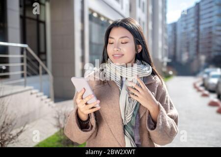 Brunette femme en manteau beige debout à l'extérieur, vérifiant son téléphone Banque D'Images