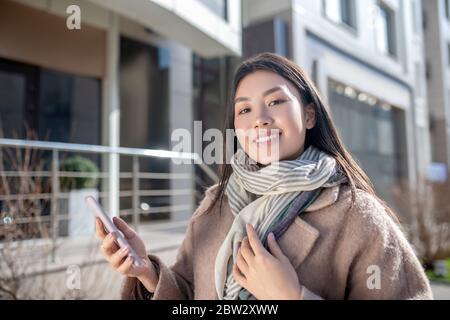 Brunette femme en beige manteau debout à l'extérieur, vérifiant son téléphone, souriant Banque D'Images