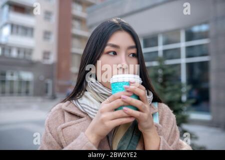 Brunette femme au pelage beige tenant une tasse de café, en appréciant sa boisson à l'extérieur Banque D'Images