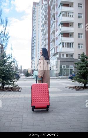 Brunette femme en beige manteau marchant avec une valise rouge le long de la rue Banque D'Images