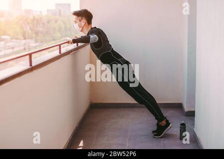 Jeune sportif homme dans masque protecteur faisant des exercices de poussée à la maison. Sportif confiant homme de forme physique dans l'entraînement médical masque de formation