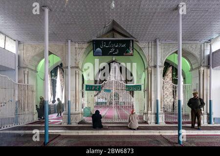 Le personnel de sécurité garde le célèbre sanctuaire de Hazratbal à Srinagar tandis qu'une femme musulmane offre des prières Banque D'Images