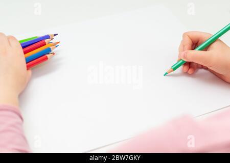 Petites mains d'enfant tenant un crayon vert sur du papier noir et un bouquet de crayons de couleur dans sa main. Copier l'espace. Banque D'Images
