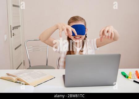 jeune fille en colère apprenant le toucher dactylographiant sur le clavier, la fille est dactylographiée avec les yeux fermés portant le masque de sommeil