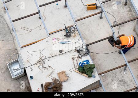 Un ouvrier de construction soudant une structure carrée à profil métallique, vue d'extérieur en grand angle