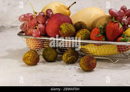 Assortiment de fruits exotiques dans un panier métallique isolé sur blanc Banque D'Images