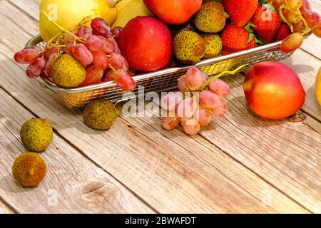 Assortiment de fruits exotiques dans un panier métallique isolé sur le bois Banque D'Images