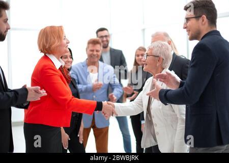 Les femmes se secouent la main à la réunion dans le hall de bureau