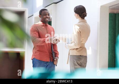 Portrait d'un homme afro-américain souriant qui se secoue avec une femme de direction tout en commençant un nouveau travail dans un bureau moderne, un espace de copie Banque D'Images