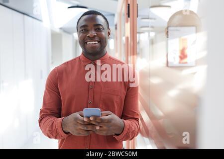 Portrait de l'homme afro-américain contemporain tenant un smartphone et souriant devant l'appareil photo, debout dans un bureau futuriste, Copy spa