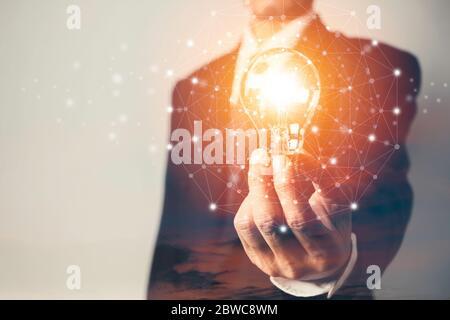 Homme d'affaires tenant une ampoule avec ciel et un espace de copie pour la comptabilité, les idées et le concept créatif.