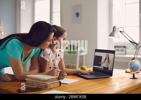 École en ligne. La mère de famille et la fille regardant la leçon professeur de conférence assis à distance à la table à la maison. Banque D'Images