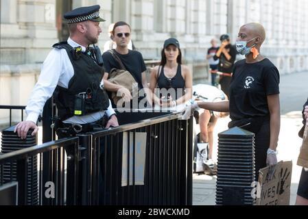 Londres, Royaume-Uni. 31 mai 2020. Un policier (L) s'entretient avec un manifestant lors d'une manifestation à propos de la mort de George Floyd devant Downing Street à Londres, en Grande-Bretagne, le 31 mai 2020. Malgré l'interdiction des rassemblements de masse en Grande-Bretagne, des milliers de personnes se sont rassemblées dimanche à Londres et à Manchester pour protester contre la mort de George Floyd, un homme noir non armé étouffé à mort par un policier blanc dans l'État du Minnesota, dans le centre-ouest des États-Unis, lundi. Crédit: Xinhua/Alay Live News