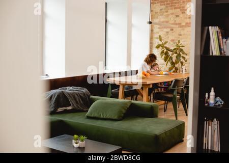 foyer sélectif de mère maurique assis près de la fille et des fruits à la maison Banque D'Images