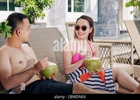 Un jeune couple vietnamien souriant se repose sur des chaises longues au bord de la piscine et propose des cocktails rafraîchissants à la noix de coco Banque D'Images