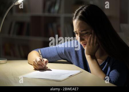 Une femme triste et inquiète signe un contrat la nuit assise dans le salon à la maison