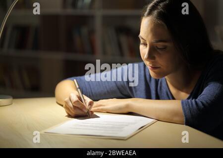 Une femme sérieuse signe un contrat la nuit dans le salon à la maison