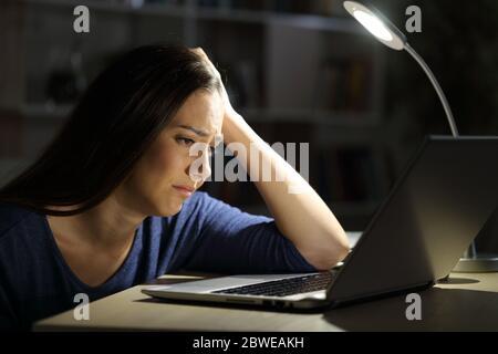 Triste femme regardant un ordinateur portable se plaignant de s'asseoir seule la nuit à la maison