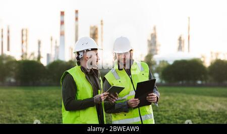Deux jeunes ingénieurs avec une tablette à l'extérieur près d'une raffinerie de pétrole, discutant des problèmes.