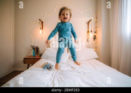 petit garçon blond a l'amusement sauter et jouer sur un grand lit. famille à la maison. coronavirus. quarantaine.