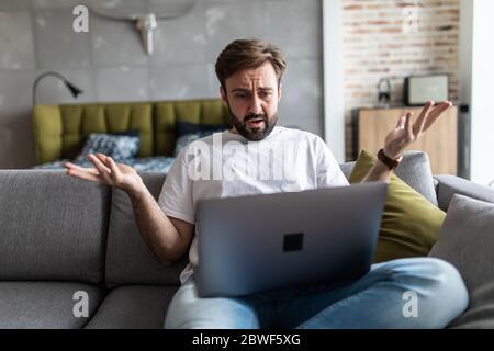 Indigné, homme en colère lisant de mauvaises nouvelles, regardant l'écran, ayant des problèmes avec un ordinateur portable cassé Banque D'Images