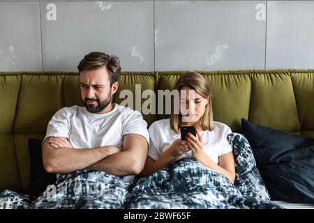 Confus de droits à propos de mobile phone while Lying in Bed Banque D'Images
