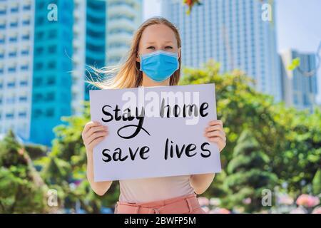 La femme dans le masque médical prévient la maladie du coronavirus tient une affiche rester à la maison sauver des vies texte écrit à la main - lettrage isolé sur blanc. Coronovirus