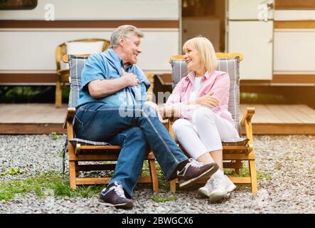 Couple marié mature se relaxant dans des chaises longues devant une camionnette de camping à l'extérieur Banque D'Images