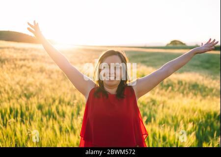 Les jeunes femmes sont soulevées jusqu'au ciel, célébrant la liberté. Émotions positives sentir la vie perception succès, paix de l'esprit concept. Fille heureuse gratuite dans un pré d'été profitant du coucher de soleil dans la nature .