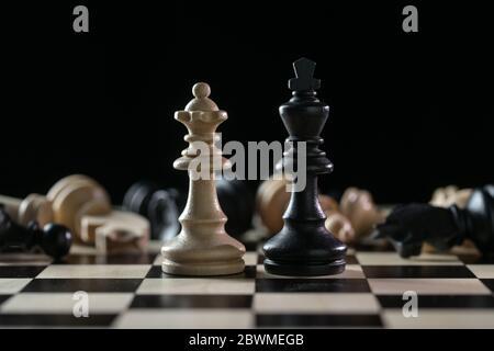 Pièces d'échecs reine et roi devant un des échiquier tombés après un champ de bataille sur un échiquier sur fond noir, concept d'abus de pouvoir
