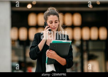 une jeune femme d'affaires parle au téléphone dans la rue