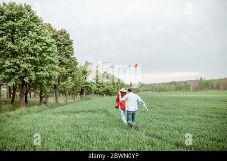Couple heureux s'amuser ensemble, jouer avec le cerf-volant sur le terrain de verdure. Un couple heureux attend un concept de famille de bébé et de jeune