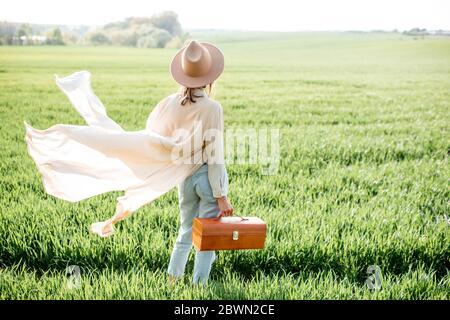 Portrait d'une femme élégante marchant avec un sac à main sur le terrain vert, profitant de la nature au printemps. Concept de bien-être et de style de vie insouciant sur la nature Banque D'Images