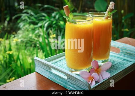 Smoothie mangue en verre avec pailles en bambou sur table en bois en extérieur, gros plan