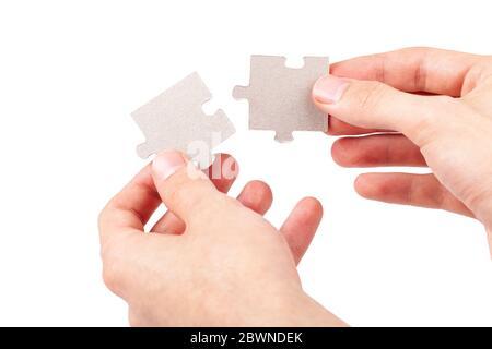 Les mains se mettent ensemble, reliant deux pièces de puzzle vierges correspondantes, joignant les pièces de raccord correspondantes, éléments isolés sur blanc, découpé Banque D'Images