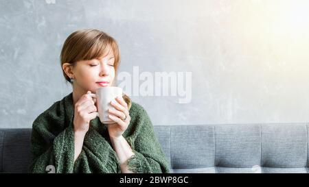 Une fille gaie à la maison tient une tasse, en appréciant ininhales l'arôme de la boisson.Homaless, Happy Home séjour et le concept de café du matin