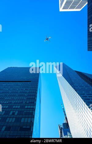 New York City, USA - 20 juin 2018 : vue à angle bas des immeubles de bureaux et des avions modernes contre le ciel dans le quartier Midtown de Manhattan.