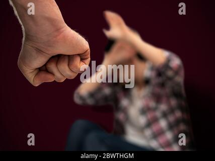 Violence domestique et abus contre les femmes. Homme agressif avec poing serré menaçant de frapper une femme effrayée. Concentrez-vous sur le poing