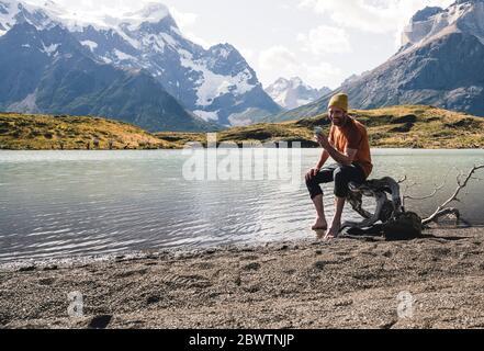 Homme utilisant un téléphone cellulaire en montagne au bord du lac dans le parc national Torres del Paine, Patagonie, Chili Banque D'Images