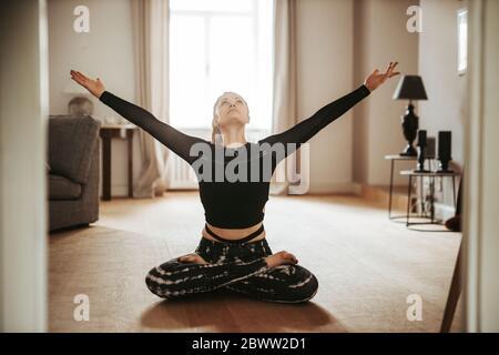 Femme assise dans une posture de lotus avec les bras levés à la maison