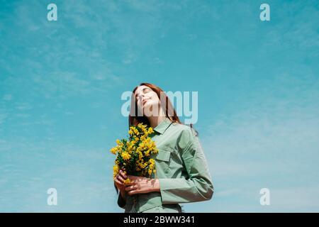 Portrait de jeune femme à tête rouge avec les yeux fermés debout contre le ciel tenant un bouquet de fleurs jaunes