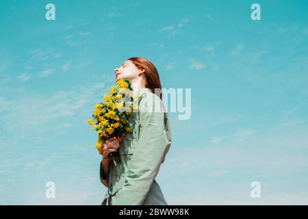 Jeune femme à tête rouge avec les yeux fermés debout contre le ciel tenant un bouquet de fleurs jaunes