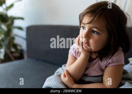 Portrait d'une fille assise sur un canapé à la maison