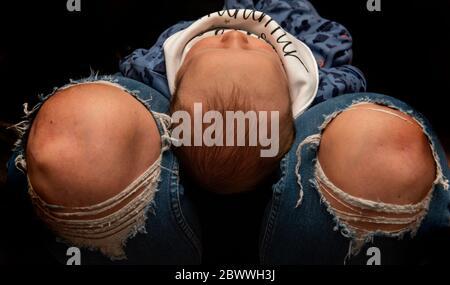 Un nouveau-né garçon avec sa tête reposant entre les jambes des mères portant un Jean denim déchiré