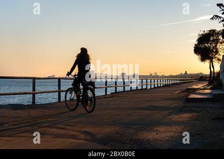 Silhouette de jeune fille maurique à vélo au coucher du soleil sur la promenade de Maresme, Catalogne, Espagne Banque D'Images