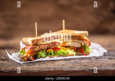 Sandwich club sur une table rustique poulet sorcière, bacon et légumes Banque D'Images