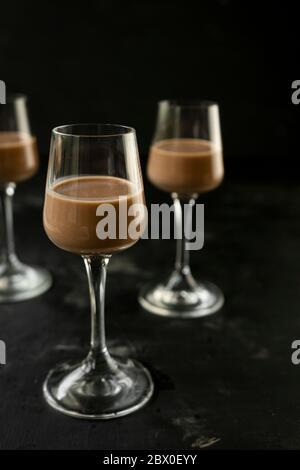 mise au point sélective : chocolat et liqueur de café dans une pile haute sur une table sombre