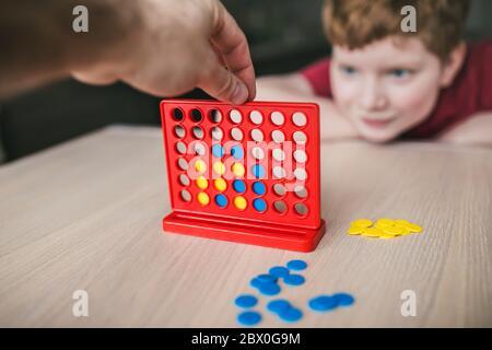 Père et fils jouant un jeu de société de 'Collect four in a line' - loisir familial