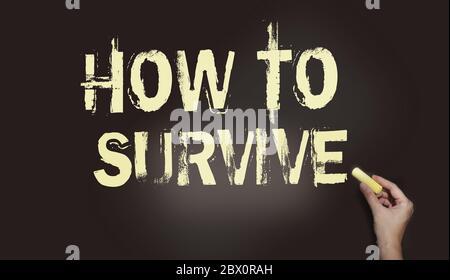 Tableau noir avec le texte Comment survivre et main avec la craie jaune. Survie dans les affaires en temps de crise concept, éviter le virus de santé concept