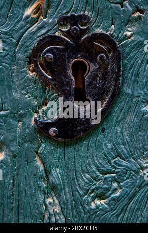 Ancienne serrure de porte en forme de coeur sur une porte en bois texturé peinte en bleu Banque D'Images